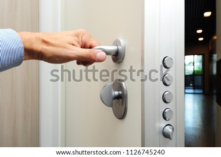 security door - hand close and open the door - security against theft in the apartment - entry and exit #1126745240