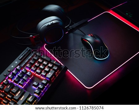 gamer workspace concept, top view a gaming gear, mouse, keyboard with RGB Color, joystick, headset, webcam, VR Headset on black table background. #1126785074