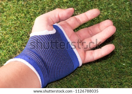 Male hand with blue wrist or palm support. #1126788035