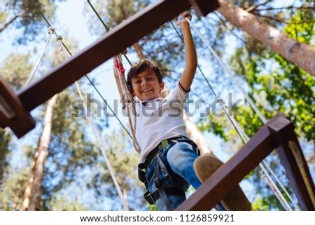 Fun experience. Cheerful preteen boy climbing the bars at an adventure park and looking down while smiling at the camera #1126859921