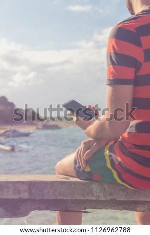 Man using cellphone on the ocean shore. #1126962788