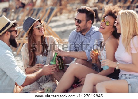 Young friends enjoying a beach party with music and drinks. #1127019845