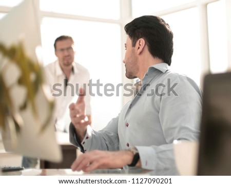 business man talking to a colleague sitting at his Desk #1127090201