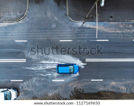 blue car on wet street after heavy rain. splashes and puddles on flooded road. aerial view #1127169650