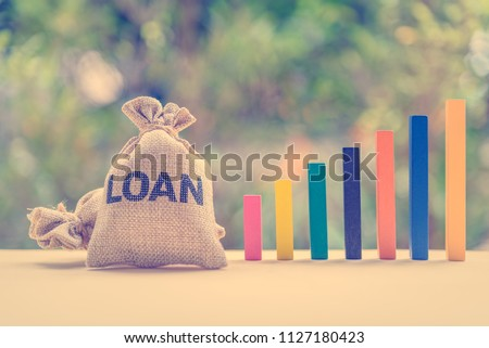 Loan or lending cash to buy asset concept : Loan bag and color wood bar graphs in different height on a table, depicts a borrower always borrow money from lender in higher amount and never payback #1127180423