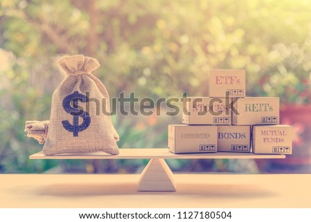 Portfolio management and asset allocation concept : Dollar bag, financial products on balance scale e.g ETFs, REITs, stocks, commodities, bonds, mutual funds, depicts balancing between risk and return #1127180504