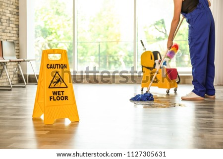 Safety sign with phrase Caution wet floor and cleaner indoors. Cleaning service #1127305631
