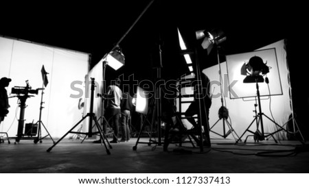 Blurred images of behind the scenes TV commercial movie film or video shooting production which crew team and camera man setting up green screen for chroma key technique in big studio.
