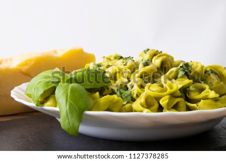 italian pasta dish prepared with cheese, vegetables and basil leaf #1127378285