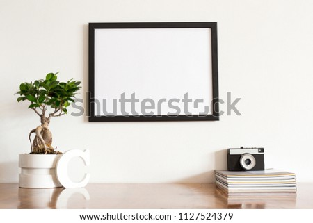 Stylish home decor interior of wooden table photo frame mock up, books, bonsai tree, camera and decorations.