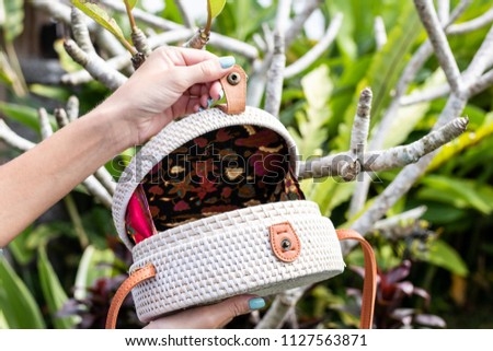 Fashionable stylish rattan bag in the tropical garden. #1127563871