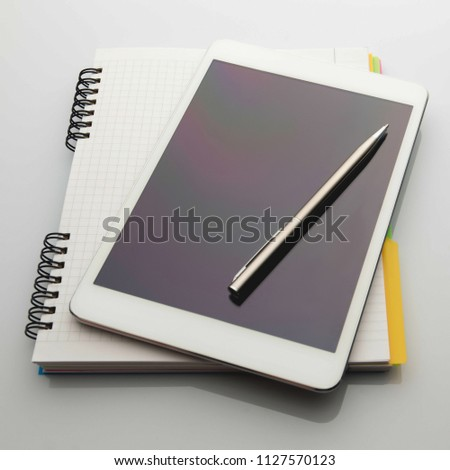 White tablet, notebook, and metal pen lie on a white background #1127570123