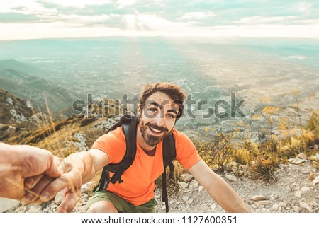 Man trekking in the mountains. Mountaineer walking on the mountain.Man on the mountain holding a hand #1127600351