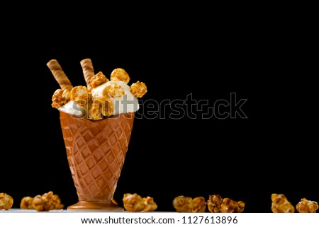 Ice cream with caramel and popcorn on a white table on a white background #1127613896