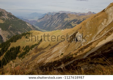 Hiking trail to the Rappenseehütte next to the lake Rappensee in the mountains of the German Alps on an autumn day. View over the mountains Rappenkopf and other mountain peaks in Germany and Austria #1127618987