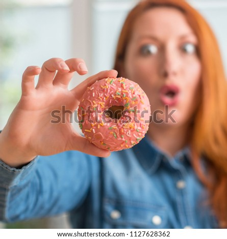 Redhead woman holding donut at home scared in shock with a surprise face, afraid and excited with fear expression #1127628362