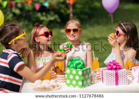 holidays, childhood and celebration concept - happy kids in sunglasses sitting at table on birthday party at summer garden and eating cupcakes #1127678486