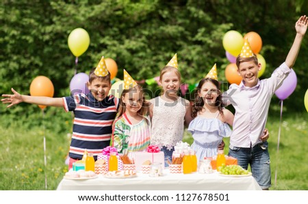 holidays, childhood and celebration concept - happy kids hugging on birthday party at summer garden #1127678501