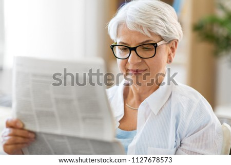 age and people concept - portrait of senior woman reading newspaper at home #1127678573