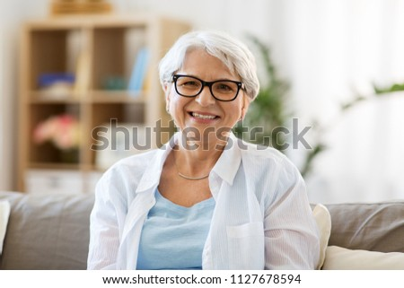 vision, age and people concept - portrait of happy senior woman in glasses #1127678594