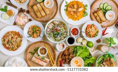 Assorted asian dinner, vietnamese food. Pho ga, pho bo, noodles, spring rolls Royalty-Free Stock Photo #1127731082