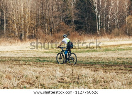 April 15, 2018, Krevo, Belarus.Beetle Trail Krevo A man runs alongside a riding bicyclist #1127760626