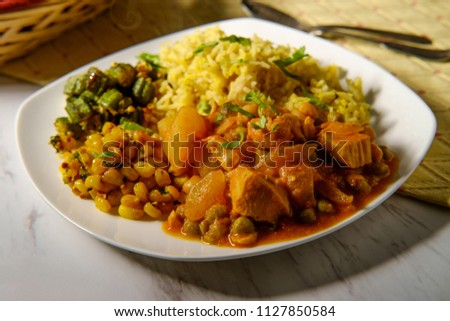 Indian chicken vegetable curry dinner with fried okra biryani rice and corn  #1127850584