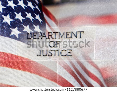 Department of Justice building sign with an American flag behind it #1127880677