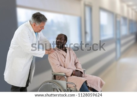 African male doctor greeting recovering senior patient in wheelchair in hospital #1128059624