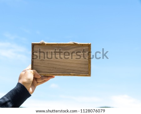 Wooden  picture  frame  in  a  hand   of  woman  with  blue  sky  background.