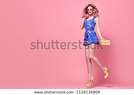 Young curly woman in floral playsuit jumping. Beautiful fashionable model girl, makeup  in trendy summer outfit. Blonde funny lady, fashion hairstyle, make up on pink. Creative style, banner #1128136808