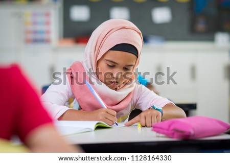 Little muslim girl wearing hijab and doing homework in class. Young arab schoolgirl in chador writing during exam in classroom. Pretty elementary child writing notes during lesson at school.