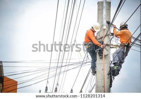 Electricians are climbing on electric poles to install and repair power lines. #1128201314