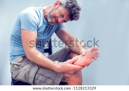 Pain in the foot, man holds hands to his feet, foot massage, cramp, muscular spasm, red accent on the foot, close-up #1128213329