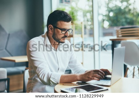 Handsome young man wearing white shirt and eye glasses sitting with laptop and working in cafe, freelance concept,close up portrait. #1128229949
