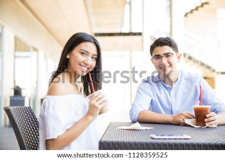 Multi-ethnic teenage couple having refreshing drinks at table in shopping mall #1128359525