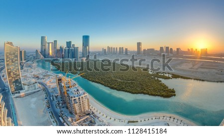 Skyscrapers on Al Reem and Al Maryah Island in Abu Dhabi at sunset timelapse from above. Aerial citiscape from Al Reem Island with modernd buildings. Orange sky and sun reflected on glass surface #1128415184