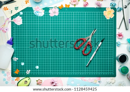 The cutting mat is surrounded by paper flowers, paper, tools and scrapbooking materials. Scrapbooking, top view #1128459425