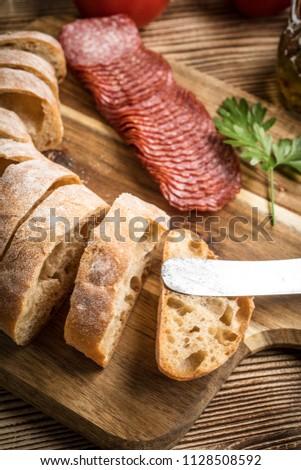 Italian ciabatta bread cut in slices on wooden chopping board with salami. #1128508592