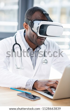 Video game. Delighted international scientist wearing VR mask while using it in technological research #1128663839