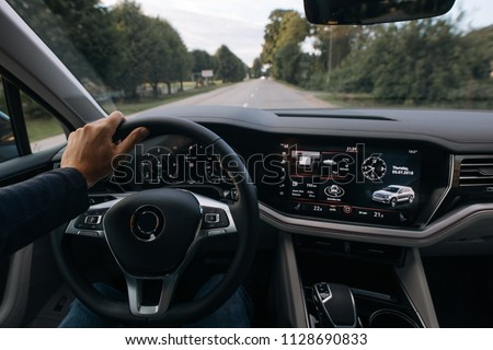 Man is driving modern suv car and holds hand on the steering wheel #1128690833