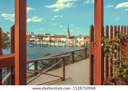 Water around city with islands, towers of Stockholm and green garden on hills of old city. Swedish landscape #1128750968