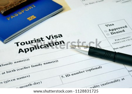 Tourist Visa application form with passport and pen. Document with passport, apply and permission for foreigner country #1128831725