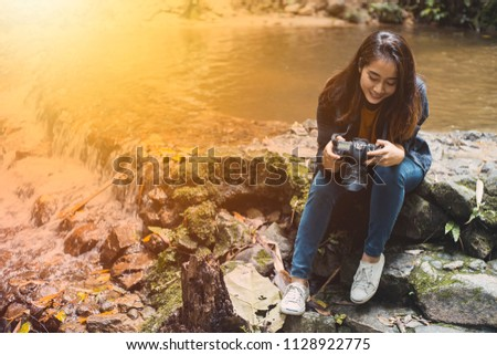 Photography and traveling Girls carrying cameras are on the waterfront in the jungle. #1128922775