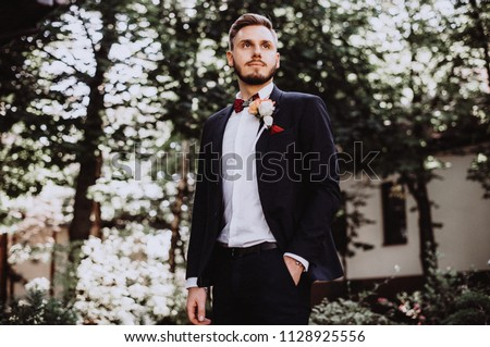 groom at wedding tuxedowaiting for bride. Rich groom at wedding day. Elegant groom in costume and bow-tie. Groom in a suit holding buttonhole. #1128925556