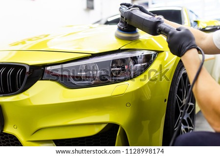 Car detailing - Worker with orbital polisher in auto repair shop. Selective focus.  Royalty-Free Stock Photo #1128998174