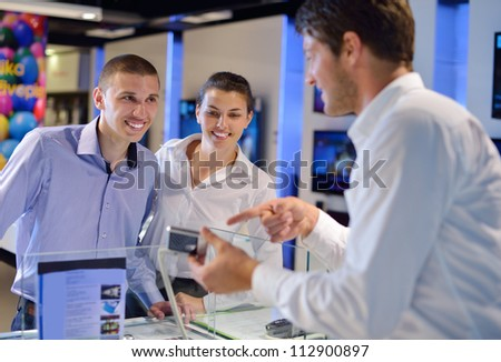 people in consumer electronics  retail store looking at latest laptop, television and photo camera to buy Royalty-Free Stock Photo #112900897