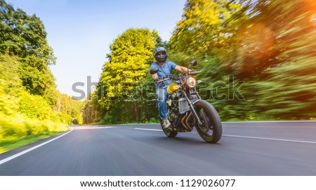 modern scrambler motorbike on the forest road riding. having fun driving the empty road on a motorcycle tour journey. Real dynamic motion blur shot. copyspace for your individual text. #1129026077