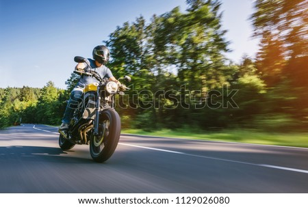modern scrambler motorbike on the forest road riding. having fun driving the empty road on a motorcycle tour journey. Real dynamic motion blur shot. copyspace for your individual text. #1129026080