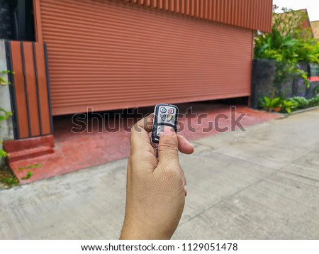 Hand holding the remote to open the sliding door.Remote control door.Electrical door.Automatic door. #1129051478